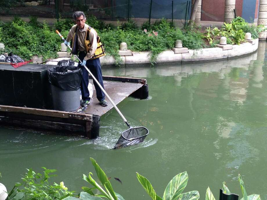 Workers from the Downtown Operations department pick up trash on the River Walk. They say they were up early picking up trash. Photo: Rebecca Salinas