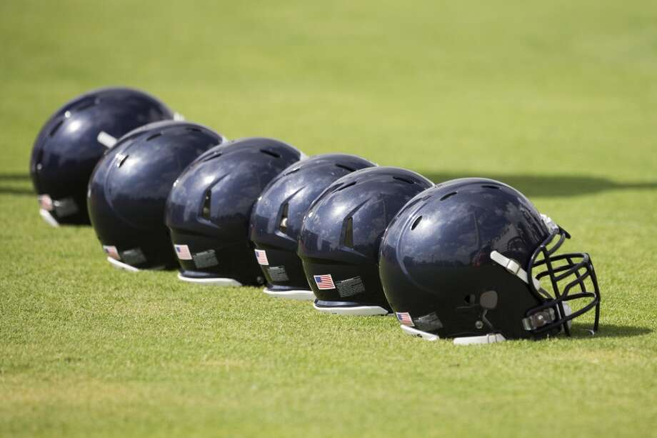 A line of helmets sit on the practice field. Photo: Brett Coomer, Houston Chronicle