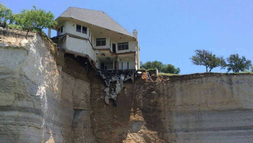 The edge of the 4,000 square foot residence on Overlook Court is dangling about 75 feet above the rocky shoreline after part of it had already broken off. Tax records show the residence, in the White Bluff Resort subdivision, was built in 2007 and is valued at more than $700,000.