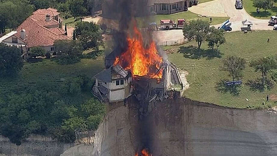 A 4,000 square foot residence on Overlook Court was set on fire after dangling about 75 feet above the rocky shoreline. Part of the home had already broken off. Tax records show the residence, in the White Bluff Resort subdivision, was built in 2007 and is valued at more than $700,000. Photo: WFAA-TV