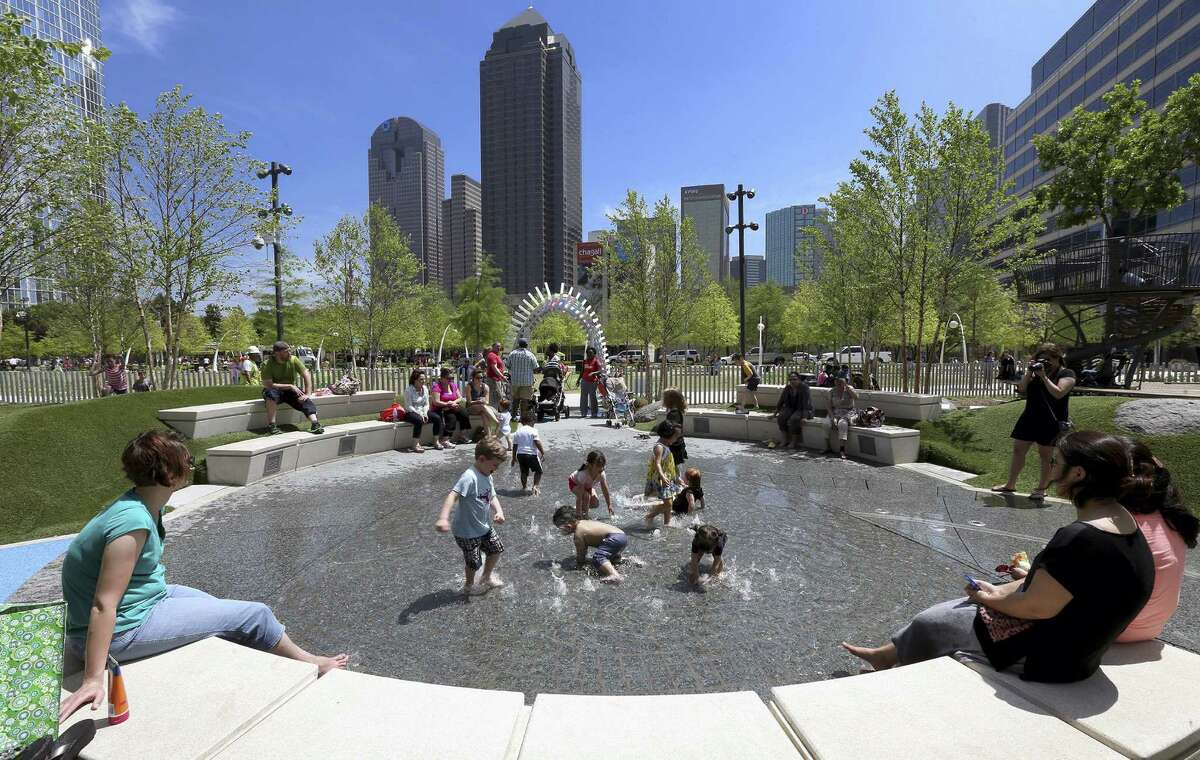 Children play in interactive fountains at Klyde Warren Park in downtown Dallas.