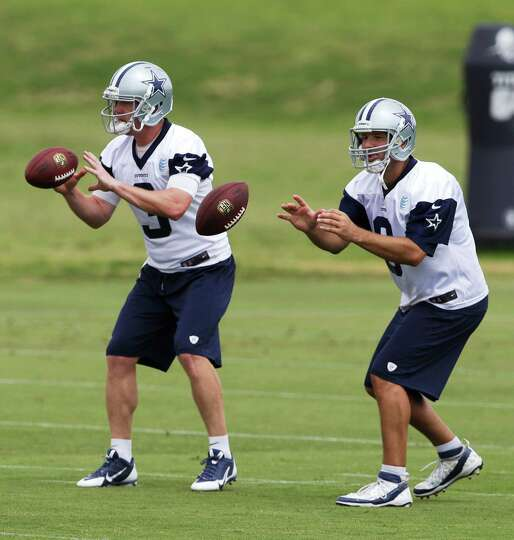 Dallas Cowboys quarterbacks Tony Romo, right, and Brandon Weeden (3) take a snap during an NFL footb