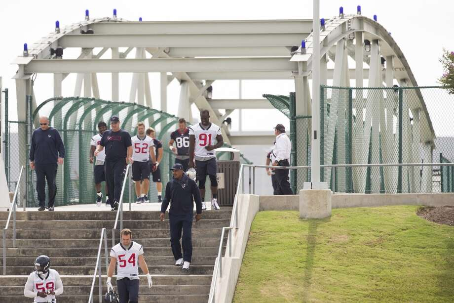 June 19  Texans players and coaches walk across the Kirby bridge to practice. Photo: Brett Coomer, Houston Chronicle
