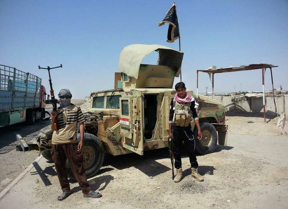 Al-Qaeda inspired militants stand with captured Iraqi Army Humvee at a checkpoint outside Beiji refinery, some 250 kilometers (155 miles) north of Baghdad, Iraq, Thursday, June 19, 2014. The fighting at Beiji comes as Iraq has asked the U.S. for airstrikes targeting the militants from the Islamic State of Iraq and the Levant. While U.S. President Barack Obama has not fully ruled out the possibility of launching airstrikes, such action is not imminent in part because intelligence agencies have been unable to identify clear targets on the ground, officials said.(AP Photo) Photo: STR / Associated Press / AP