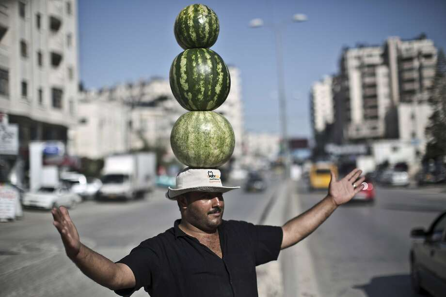 That's using his melon:Palestinian fruit vendor Shaher Abu Yamin performs a balancing act   in an effort  to attract customers near the West Bank refugee camp of Kalandia. Photo: Muhammed Muheisen, Associated Press