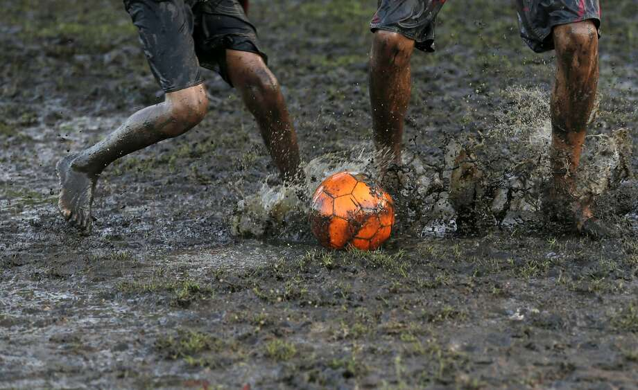 The Beautiful Game:As soccer fans around the globe watch the World Cup, children in Natal, Brazil - one of the   host cities for the tournament - play barefoot on a pitch of mud and puddles. Photo: Petr David Josek, Associated Press