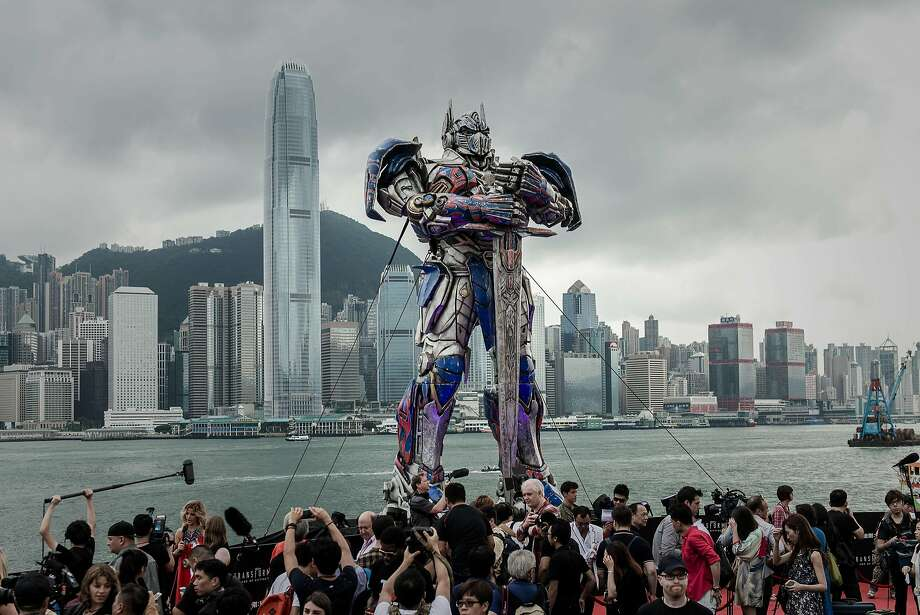 """Skyline Transformer:Reporters surround a 20-foot-tall Optimus Prime figure before the world premiere of  the movie """"Transformers: Age of Extinction"""" in Hong Kong. The Michael Bay film was   partly shot in the city. Photo: Philippe Lopez, AFP/Getty Images"""