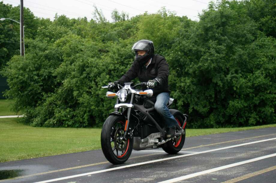 In this Wednesday, June 18, 2014 photo, employee Ben Lund demonstrates Harley's new electric motorcycle at Harley's research facility in Wauwatosa, Wis. The company plans to unveil the LiveWire model Monday, June 23, at an invitation-only event in New York. (AP Photo/M.L. Johnson) ORG XMIT: RPMJ201 Photo: M.L. Johnson / AP
