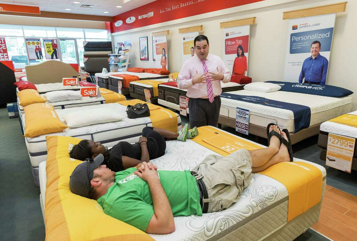 Mattress Firm at 2071 Westheimer, Ste C. Assistant Store Manager Alejandro Guerra (in pink long sleeve shirt) discusses bed options with Andy Hollister (green shirt, shorts) and Maxina Kroma (black shirt, shorts). (Craig H. Hartley/For the Chronicle)