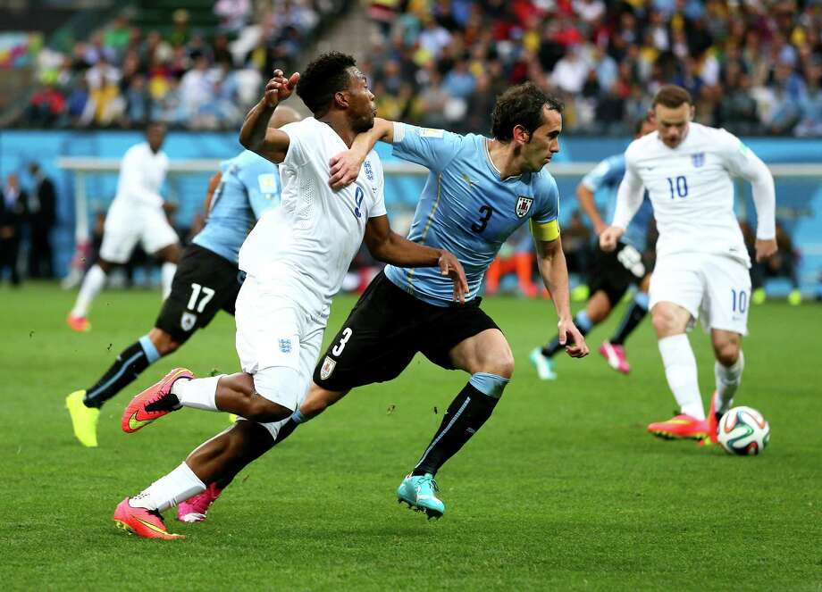 SAO PAULO, BRAZIL - JUNE 19: Diego Godin of Uruguay holds off a tackle by Daniel Sturridge of England during the 2014 FIFA World Cup Brazil Group D match between Uruguay and England at Arena de Sao Paulo on June 19, 2014 in Sao Paulo, Brazil. Photo: Kevin C. Cox, Getty Images / 2014 Getty Images