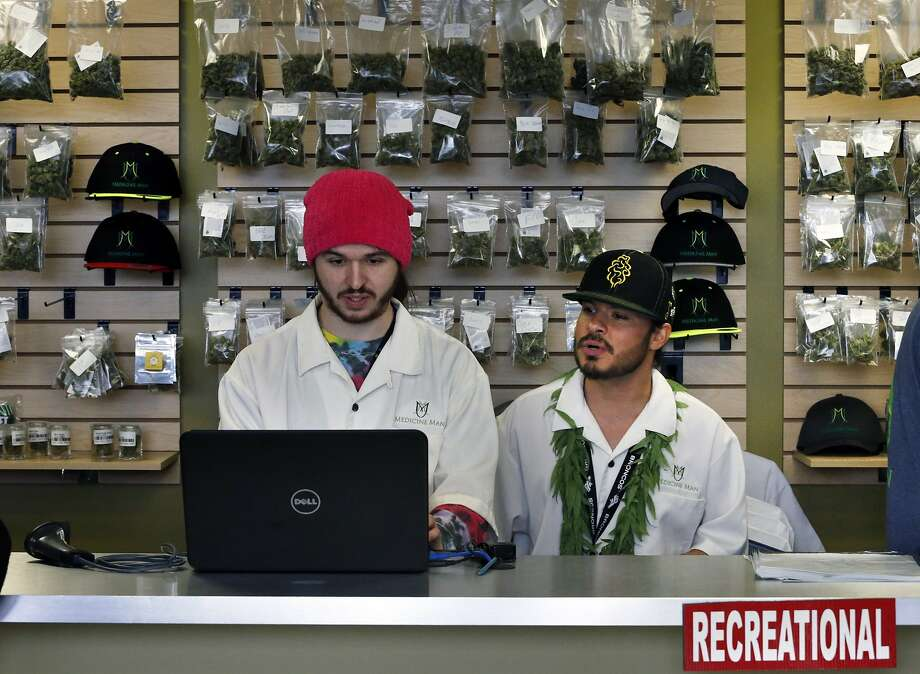 Employees Chris Broussard (left) and David Marlow work at a Denver marijuana retail store. Photo: Brennan Linsley, Associated Press
