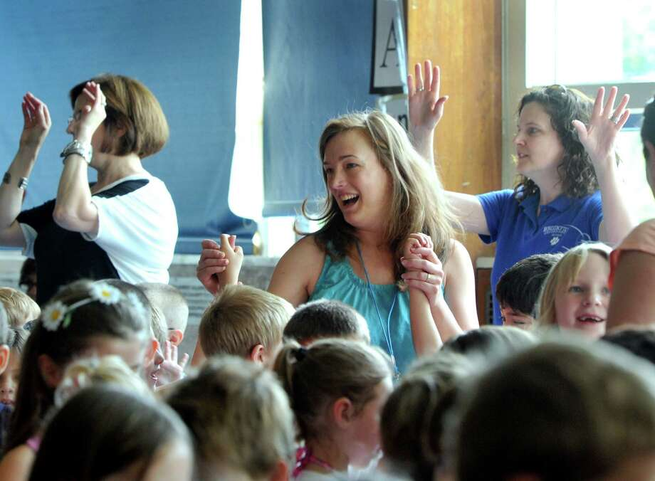 Center Elementary School in Brookfield, Conn., celebrated three retiring teachers during an all-school assembly Wednesday morning that included a procession of children with flowers, songs and dancing. The teachers are Judy Williams, a kindergarten teacher who has been in the district 44 years, and Joan Oppenheimer and Toni Sullivan, first grade teachers with 29 years in the district. Photo: Carol Kaliff / The News-Times