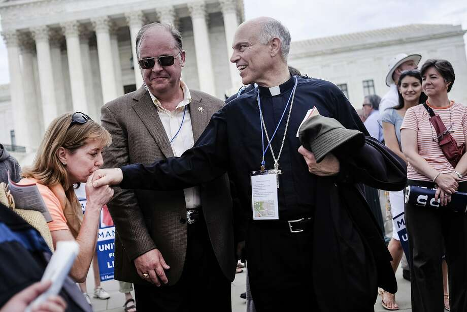 San Francisco Archbishop Salvatore Cordileone is kissed by a supporter as the March for Marriage rally ends outside the Supreme Court in Washington, DC on June 19, 2014. Speakers at the rally and march promoted the definition of marriage as between a man and a woman, and pushed back against the notion that public opinion is heavily in favor of revoking restrictions against gay marriage. 