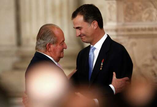 Spanish King Juan Carlos, left, embraces Spanish Crown Prince Felipe after signing an abdication law during a ceremony at the Royal Palace in Madrid, Spain, Wednesday June 18, 2014. Spain's Juan Carlos formally ratified the law, signing a legislation setting out the legal framework for the handover so his 46-year-old son can be proclaimed King Felipe VI at a ceremony in Parliament on Thursday. The 76-year-old monarch says he wants to step aside after a four-decade reign so that younger royal blood can rally a country beset by economic problems, including an unemployment rate of 25 percent. (AP Photo/Daniel Ochoa de Olza) Photo: Daniel Ochoa De Olza, Associated Press / AP