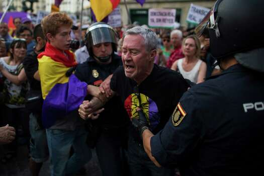 Police arrest a protestor during a demonstration against the Monarchy in Madrid, Spain, Thursday, June 19, 2014. Dozens of protestors gathered in Madrid's main square to protest against the Spanish Monarchy on the day Spain's King Felipe VI was crowned. The Spanish Government unauthorized any kind of protest against the Spanish monarchy and police cordoned off the city centre. Felipe's father Juan Carlos, who reigned during four decades, stepped down after signing an abdication law Wednesday so that younger royal blood can rally a country beset by economic problems, including an unemployment rate of 25 percent. (AP Photo/Andres Kudacki) Photo: Andres Kudacki, Associated Press / AP
