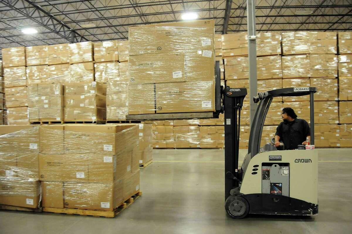 Marco Santa Maria stacks pallets of coolers at Igloo's new warehouse Friday May 30, 2014.(Dave Rossman photo)