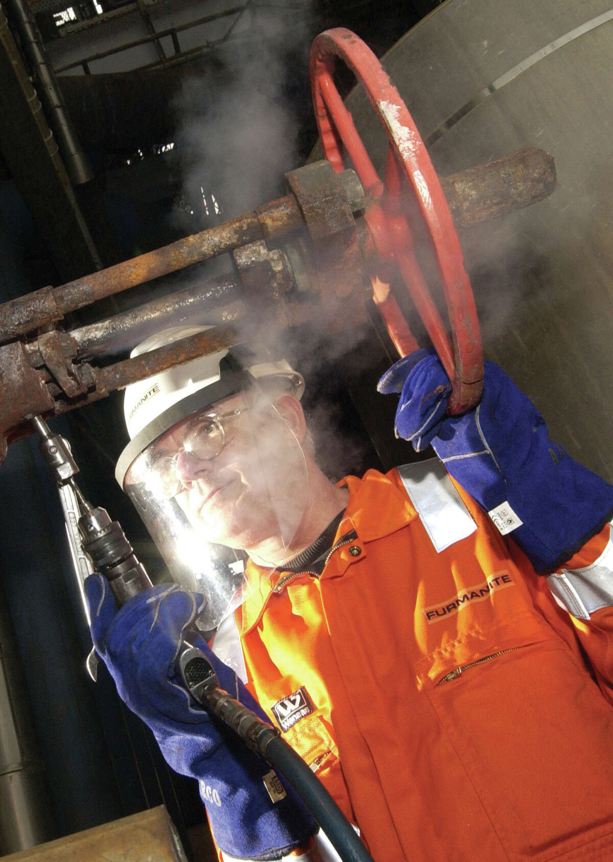 A furmanite service technician seals a leak in a valve, using their proprietary compound, at a process plant.