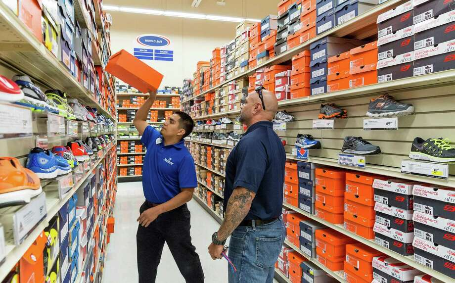 Pedro Lopez helps customer Robert Gonzales choose running shoes at the Academy at 9734 Katy Freeway. Academy has emphasized multichannel retailing. Photo: Craig Hartley, Freelance / Copyright: Craig H. Hartley