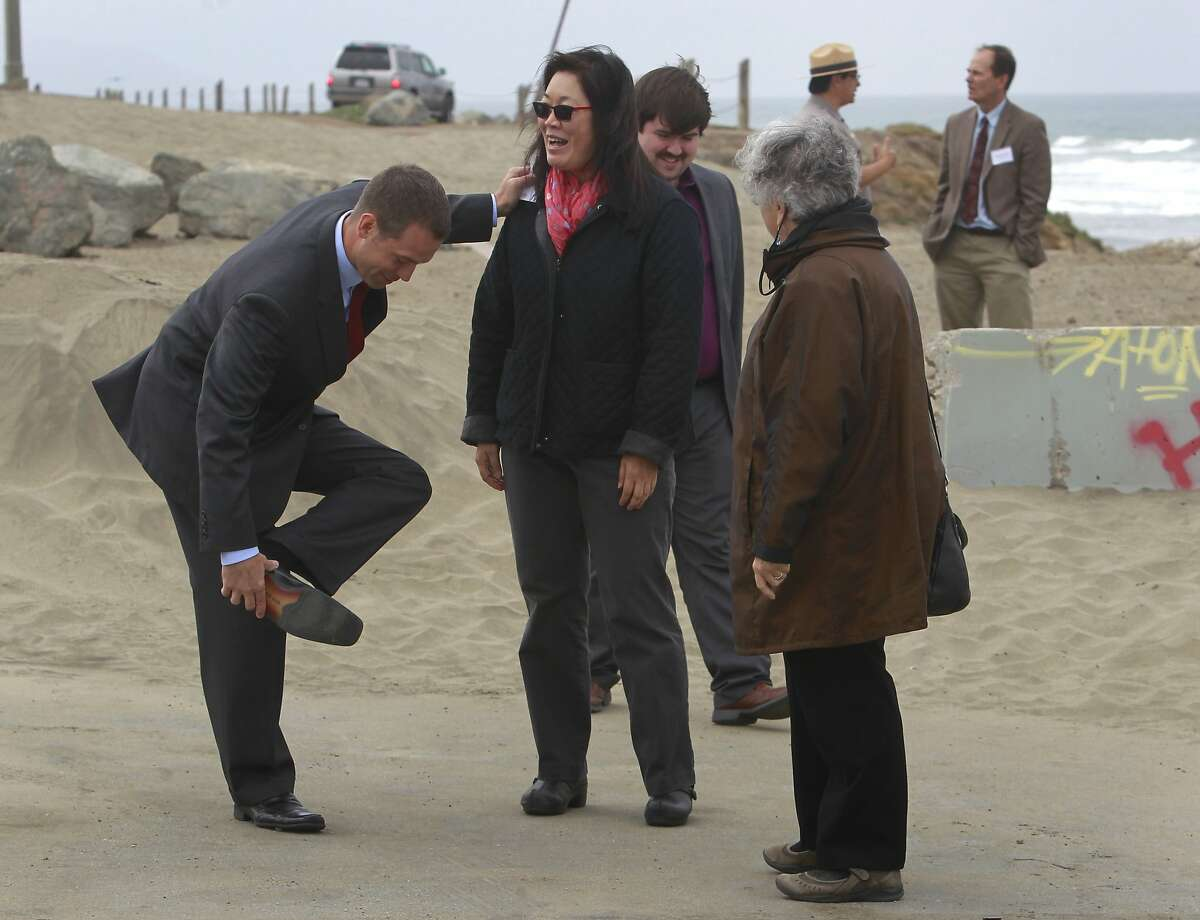 Mike Boots, acting chair of the White House Council of Environmental Quality, balances on Nancy Woo, of the United States EPA, to remove sand from his shoe after a tour of Ocean Beach in San Francisco, Calif. on Thursday, June 19, 2014. Boots was updated on the city's Ocean Beach Master Plan, which outlines a comprehensive, long-term vision over the next 40 years to address sea level rise, protect critical wastewater infrastructure, restore coastal ecosystems, manage a changing coastline, and improve public access to the beach.