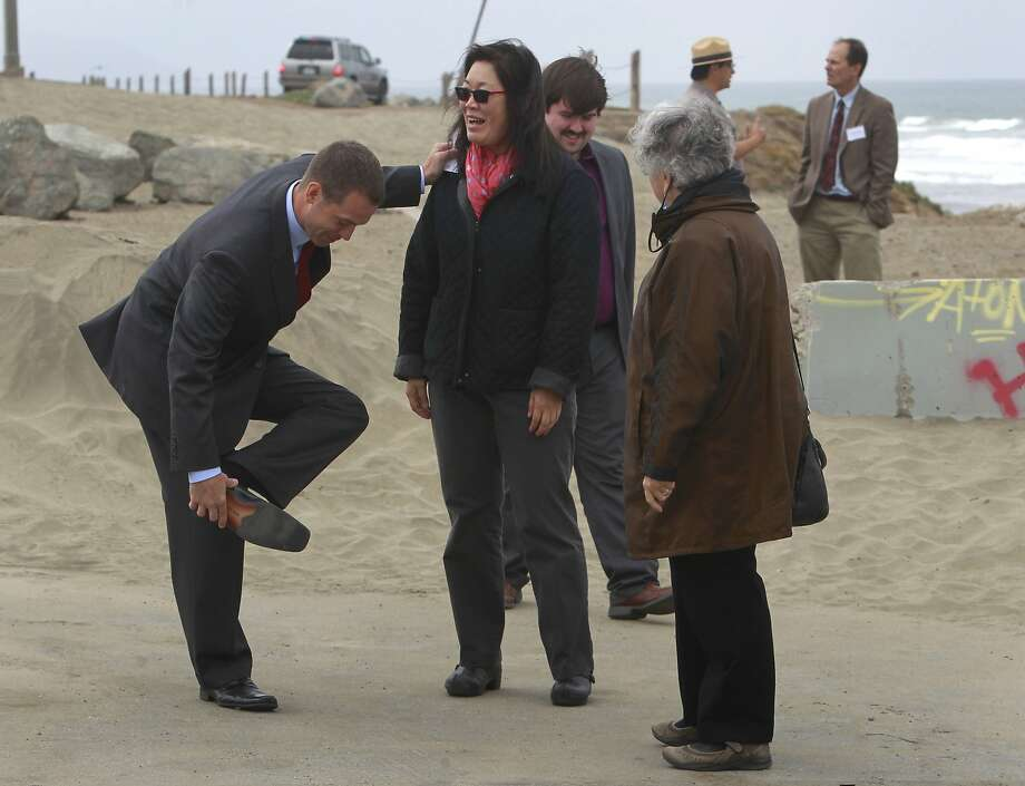 White House aide Mike Boots holds on to EPA's Nancy Woo to remove sand from his shoe at Ocean Beach. Photo: Paul Chinn, The Chronicle