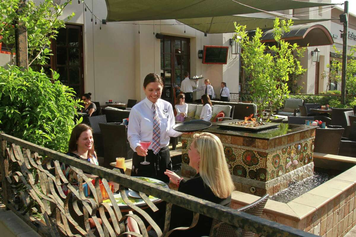 (For the Chronicle/Gary Fountain, May 22, 2014) Raquel Rios, center, serving Jenny Hung, left, and Carlin Putman on the patio dinning area at Grotto restaurant on Westheimer.