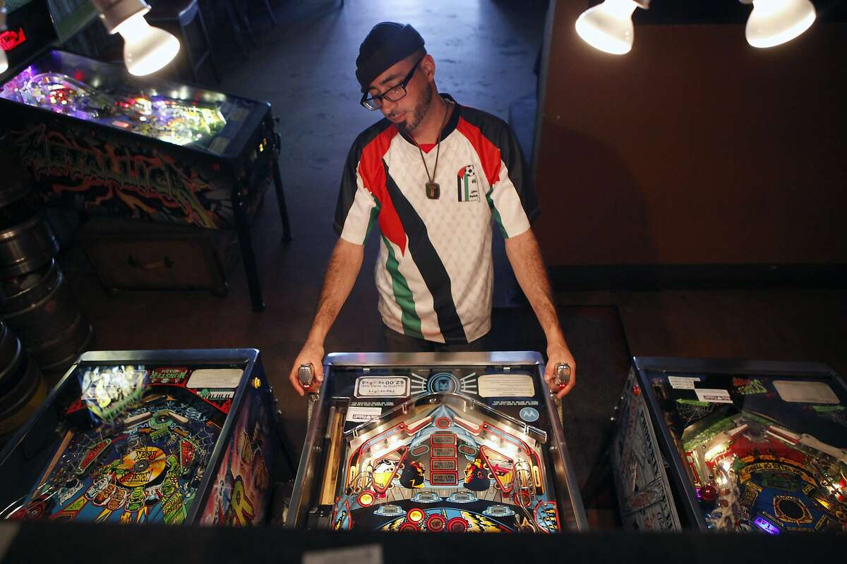 Tarik Kazaleh of Oakland plays the Demolition Man pinball machine at The Legionnaire bar in Oakland, CA, Thursday June 19, 2014. The city of Oakland is preparing to remove an archaic law from the books that put a ban on playing pinball machines.