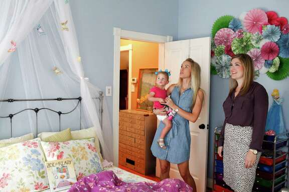 Stephanie Finch, right, of Martha Turner Southeby's International Realty shows a house in the Heights to Casey Scott and her daughter Lyla, 1, June 4, 2014 in Houston.  (Eric Kayne/For the Chronicle)