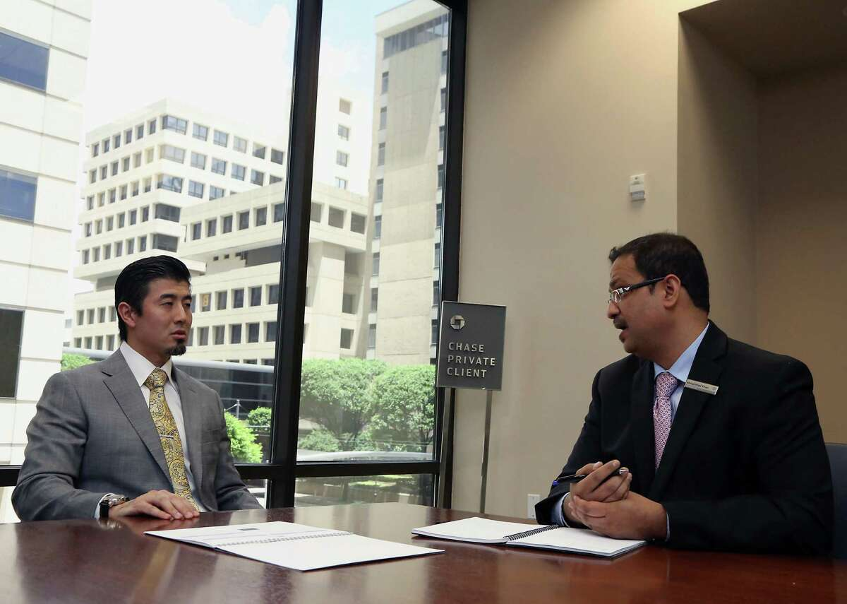 Chase Private Client Banker Mohammad Khan right, sets up a future meeting client Dimitri Ang Friday, June 6, 2014, in Houston. ( James Nielsen / Houston Chronicle )