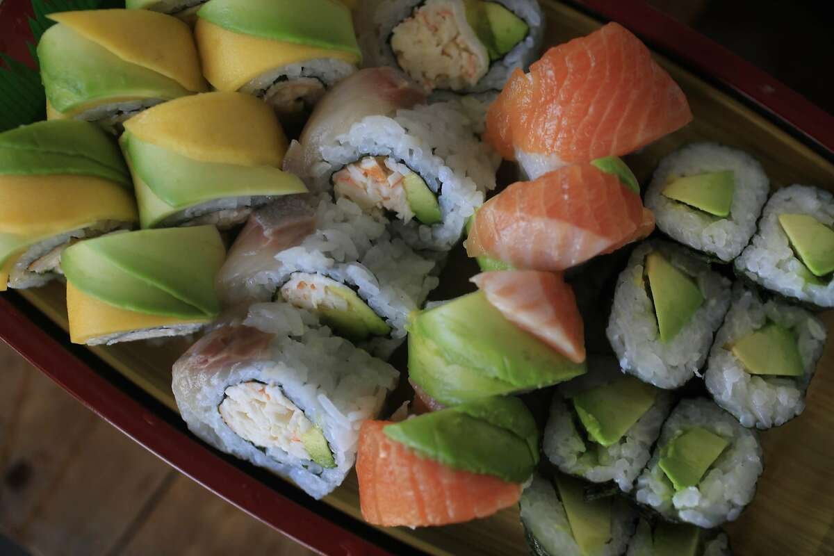 California rolls with different toppings such as sashimi, mango and avocado along with avocado maki are displayed in a wooden serving boat at L'Chaim Sushi on Tuesday, May 27, 2014 in South San Francisco, Calif.