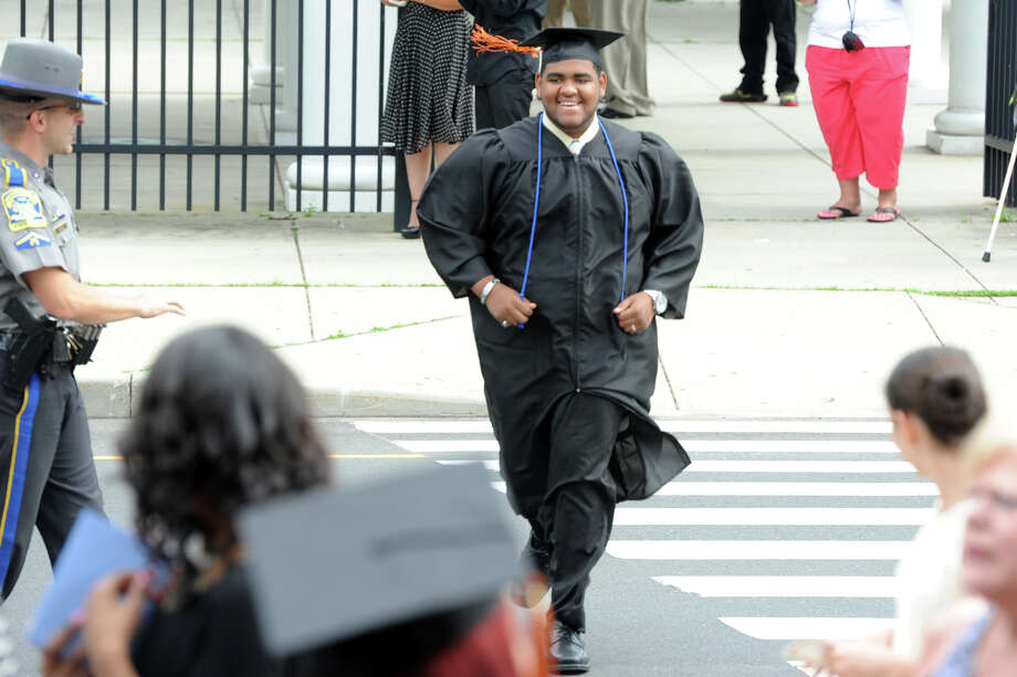 Clive Higgins, from the Carpentry Programs, runs across Fairfield Ave. as he arrives for Commencement Exercises for the Bullard-Havens Technical High School Class of 2014, held at The Klein Memorial Auditorium, in Bridgeport, Conn. June 19, 2014. Photo: Ned Gerard / Connecticut Post