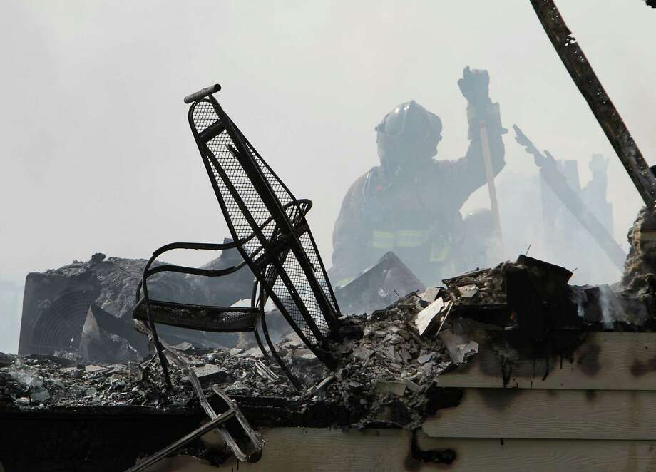 A Houston Fire Department firefighter works at the scene of a 2-alarm fire at the Vintage Apartments Thursday, June 19, 2014, in Houston. Photo: James Nielsen, Houston Chronicle / © 2014  Houston Chronicle