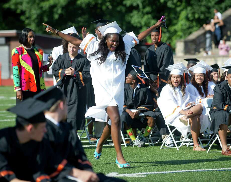 Stetya Jean Baptiste dances her way to the podium to get her diploma during the Stamford High School commencement ceremony on Thursday, June 19, 2014. Photo: Lindsay Perry / Stamford Advocate