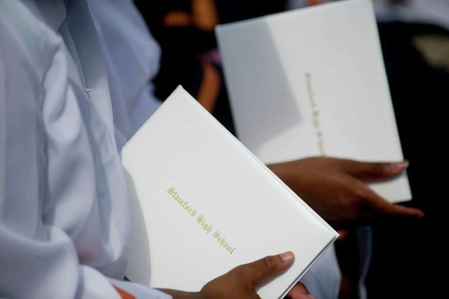 Graduates hold their diplomas during the Stamford High School commencement ceremony on Thursday, June 19, 2014. Photo: Lindsay Perry / Stamford Advocate