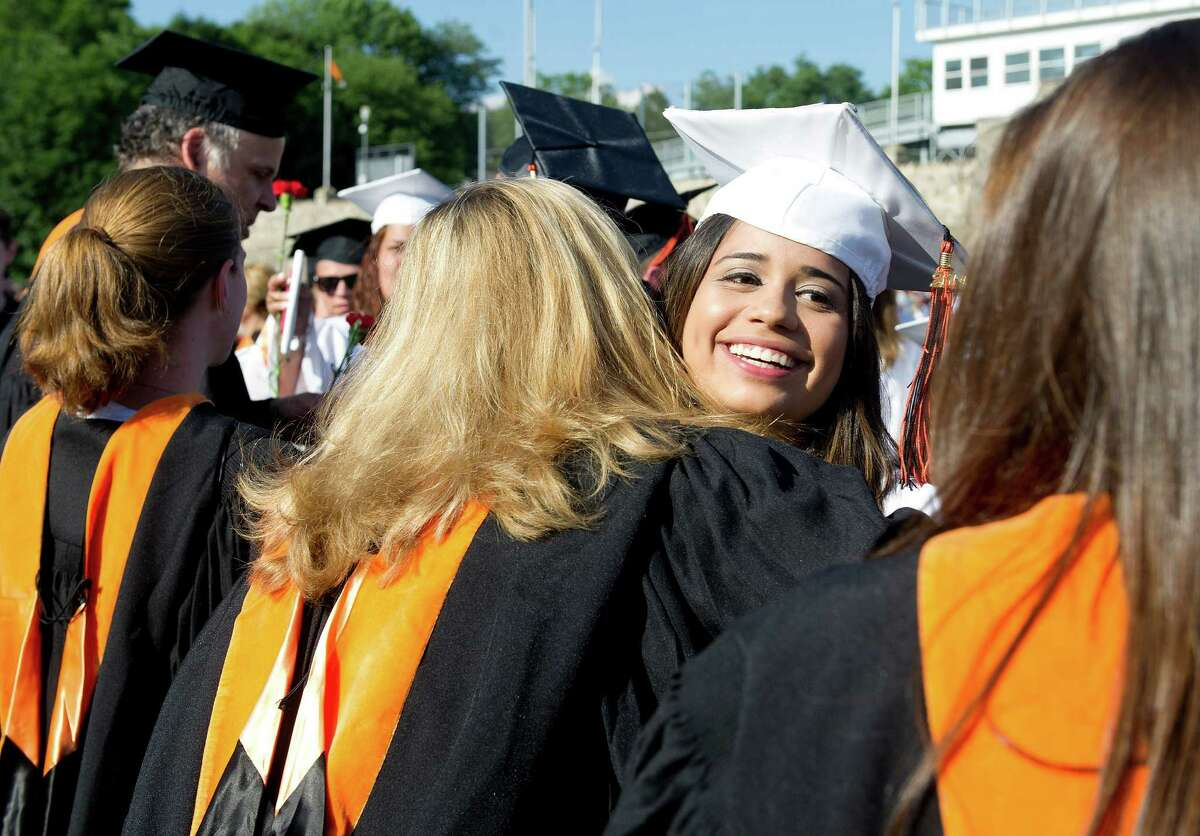 Graduates hug teachers during the recessional during the Stamford High School commencement ceremony on Thursday, June 19, 2014.