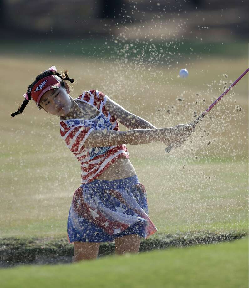 Lucy Li blasts from a bunker on No. 13. The 11-year-old missed only one fairway in her round of 78, 11 shots off the lead. Photo: Bob Leverone, Associated Press