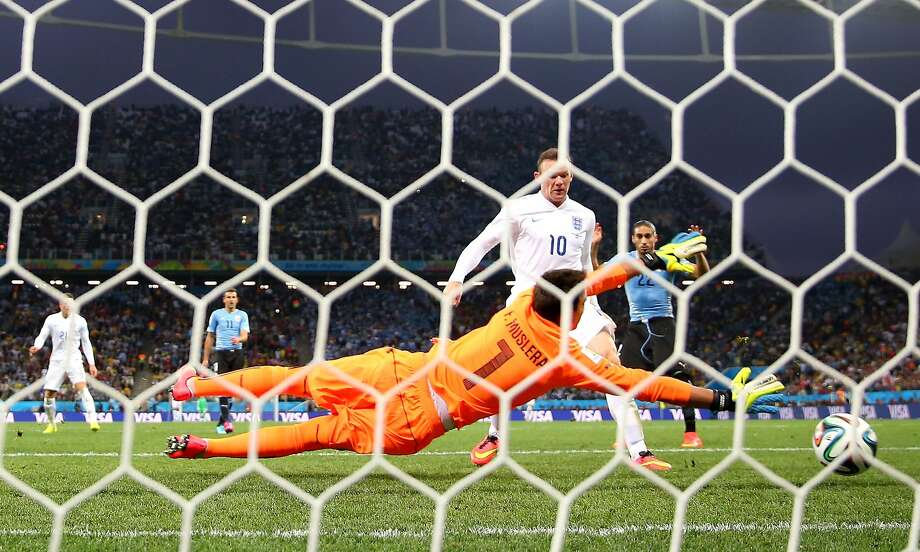 Wayne Rooney, one of England's greatest-ever stars, scores his first World Cup goal ever, blasting it past Uruguay goalkeeper Fernando Muslera. But England lost 2-1 and likely will not advance. Photo: Richard Heathcote, Getty Images