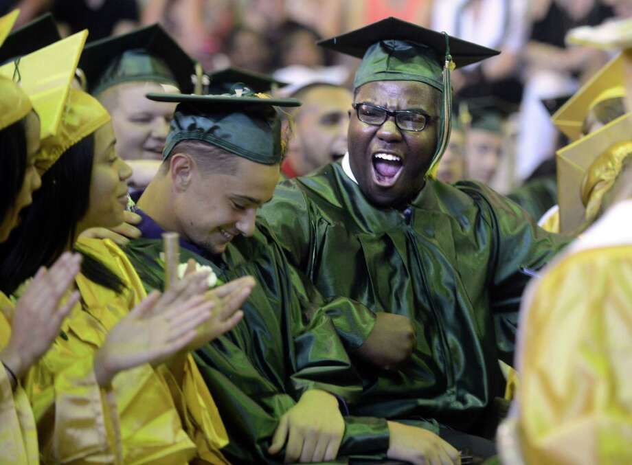Graduate Capell Bacote, of Ansonia, cheers for his friend Daniel Maisonave, left, of Ansonia, during the Emmett O'Brien Technical High School commencement ceremony Thursday, June 19, 2014 at the school in Ansonia, Conn. Photo: Autumn Driscoll / Connecticut Post