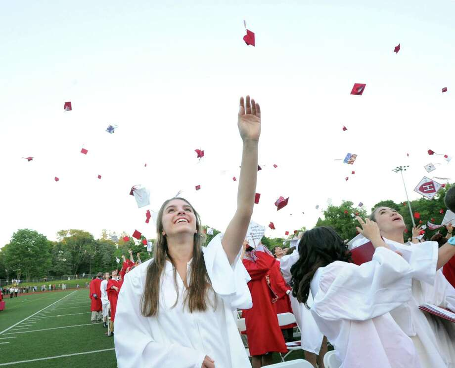 At left, Catherine Cabano, 17, tosses her graduation cap into the air with other graduates at the end of the Greenwich High School graduation ceremony at the school in Greenwich, Conn., Thursday night, June 19, 2014. Cabano said she will be attending the University of Connecticut in the fall. Photo: Bob Luckey / Greenwich Time