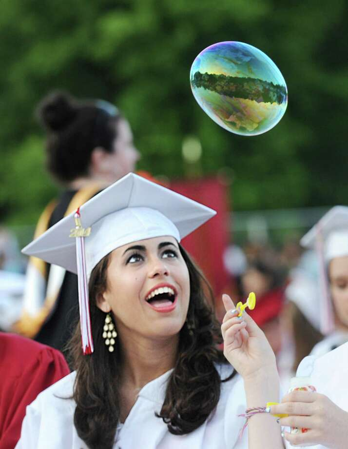 Ceciilia Estanislao, 17, smiles at the bubble blown by a fellow graduating senior during the Greenwich High School graduation ceremony at the school in Greenwich, Conn., Thursday night, June 19, 2014. Photo: Bob Luckey / Greenwich Time