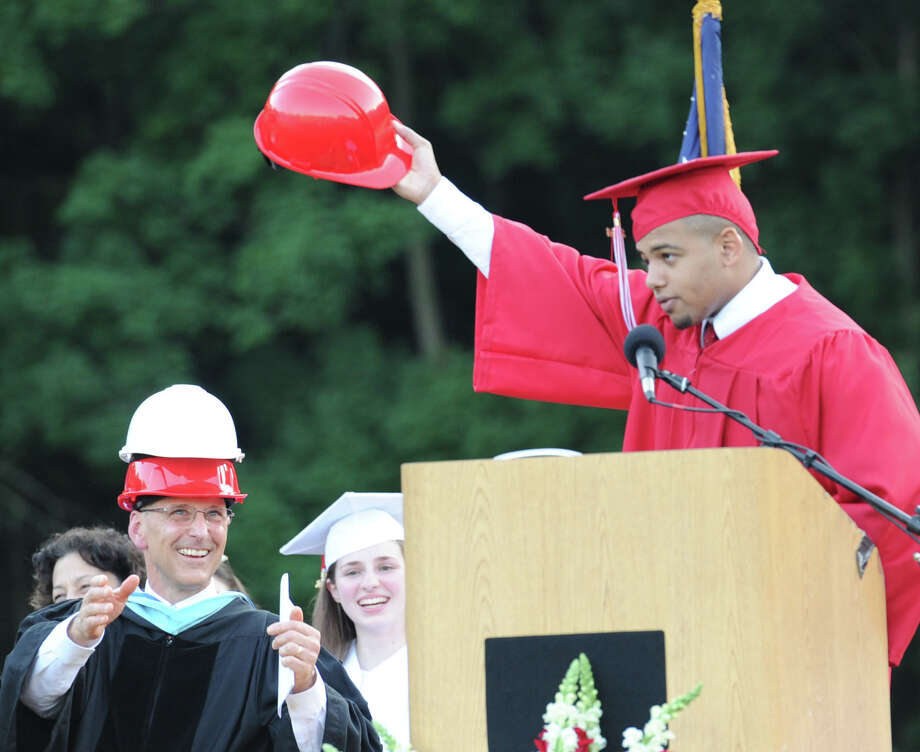 At right, Isaiah Nins, the graduating Greenwich High School 2014 Class Treasurer, gives a gift of three construction hats to Headmaster Chris Winters, at left, during the graduation ceremony at the school in Greenwich, Conn., Thursday night, June 19, 2014. Photo: Bob Luckey / Greenwich Time