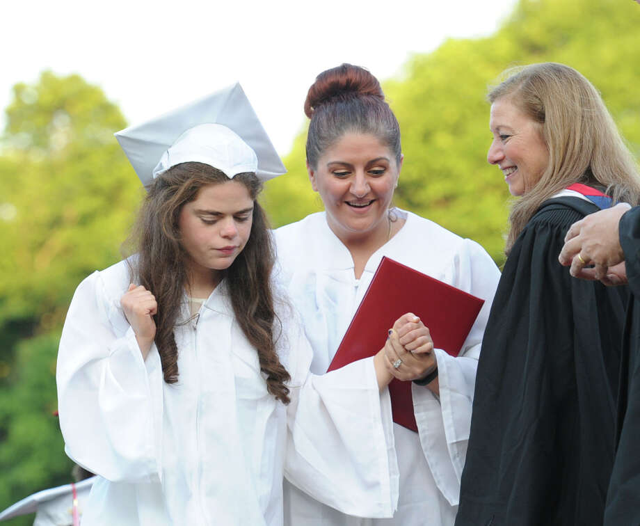 At left, Morgan Fahey, 19, receives her diploma during the Greenwich High School graduation ceremony at the school in Greenwich, Conn., Thursday night, June 19, 2014. Photo: Bob Luckey / Greenwich Time