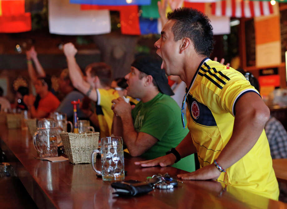 Colombian fan and native Andres Mercado, right, cheers on Colombia as they score a goal during a world cup match against Ivory Coast, inside Wolff's Biergarten in Albany, N.Y. on Thursday, June 19, 2014.  Colombia defeated Ivory Coast 2-1.  (Tom Brenner/ Special to the Times Union)  ORG XMIT: 00027420A Photo: Tom Brenner / ©Tom Brenner/ Albany Times Union