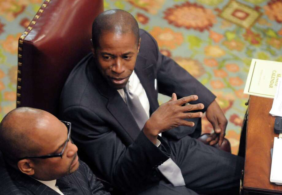 State Senator Malcolm A. Smith, right, and Senator John Sampson, left, talk in the Senate Chamber Thursday June 19, 2014, at the Capitol in Albany, N.Y.  A judge declared a mistrial in the bribery case against Sen. Smith earlier this week. Smith was accused of trying to bribe his way onto the New York City mayoral ballot.(Michael P. Farrell/Times Union) Photo: Michael P. Farrell / 00027435A