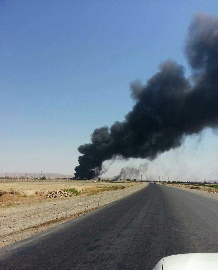 A column of smoke rises from Beiji oil refinery, some 250 kilometers (155 miles) north of Baghdad, Iraq, Thursday, June 19, 2014. The fighting at Beiji comes as Iraq has asked the U.S. for airstrikes targeting the militants from the Islamic State of Iraq and the Levant. While U.S. President Barack Obama has not fully ruled out the possibility of launching airstrikes, such action is not imminent in part because intelligence agencies have been unable to identify clear targets on the ground, officials said.(AP Photo) ORG XMIT: BAG110 / AP