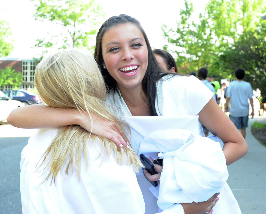 Greenwich High School graduating senior Bella Moore, 17, hugs a friend prior to the start of the Greenwich High School graduation ceremony at the school in Greenwich, Conn., Thursday night, June 19, 2014. Photo: Bob Luckey / Greenwich Time