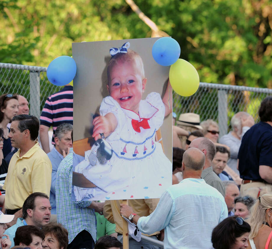 Jonas Akerman carries a billboard photo of his daughter, Greenwich High School graduate, Julia Akerman, as a baby, prior to the Greenwich High School graduation ceremony at the school in Greenwich, Conn., Thursday night, June 19, 2014. Photo: Bob Luckey / Greenwich Time