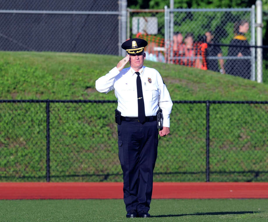 Greenwich Police Chief James Heavey salutes during the National Anthem that was played at the start of the Greenwich High School graduation ceremony at the school in Greenwich, Conn., Thursday night, June 19, 2014. Photo: Bob Luckey / Greenwich Time
