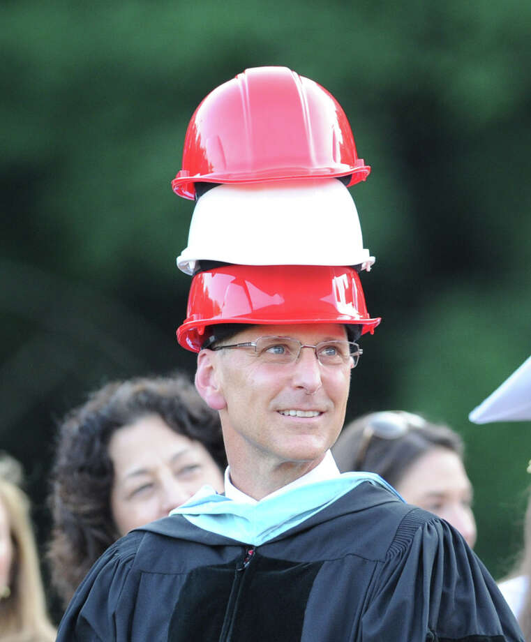 Greenwich High School Headmaster Chris Winters wears three construction hats given to him by graduating senior Isaiah Nins during the Greenwich High School graduation ceremony at the school in Greenwich, Conn., Thursday night, June 19, 2014. Photo: Bob Luckey / Greenwich Time