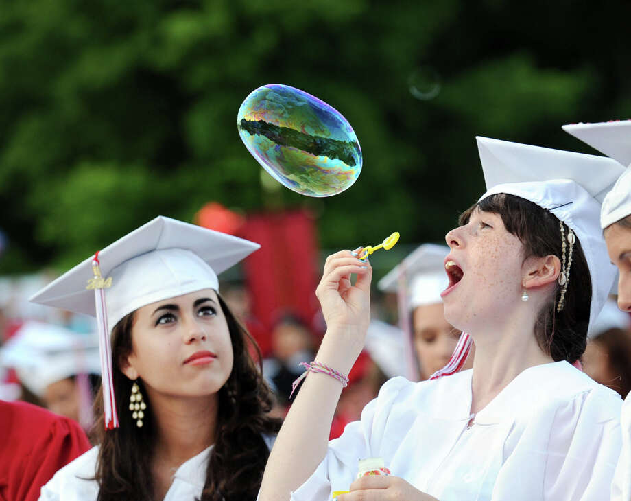 Ceciilia Estanislao, 17, left. looks at the bubble blown by a fellow graduating senior, Juliana Edelstein, 17, during the Greenwich High School graduation ceremony at the school in Greenwich, Conn., Thursday night, June 19, 2014. Photo: Bob Luckey / Greenwich Time