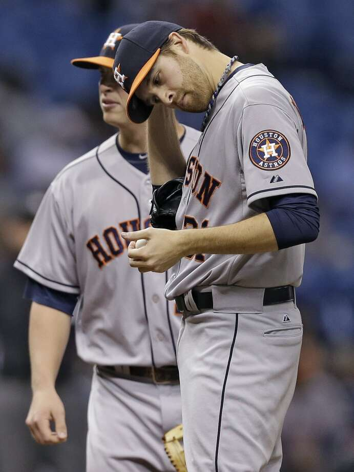 Collin McHugh, right, reacts as he waits for a visit from pitching coach Brent Strom during the third inning. Photo: Chris O'Meara, Associated Press